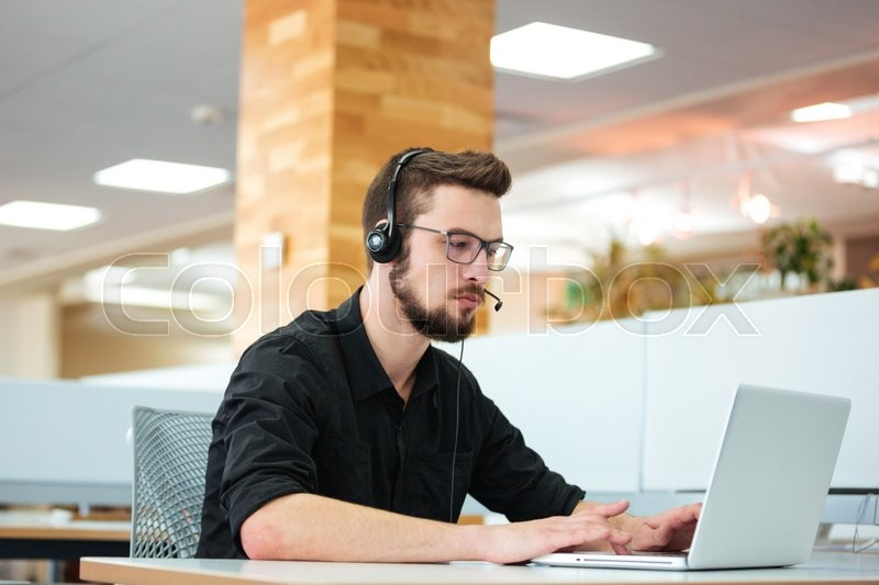 Businessman working on laptop computer in call center, stock photo