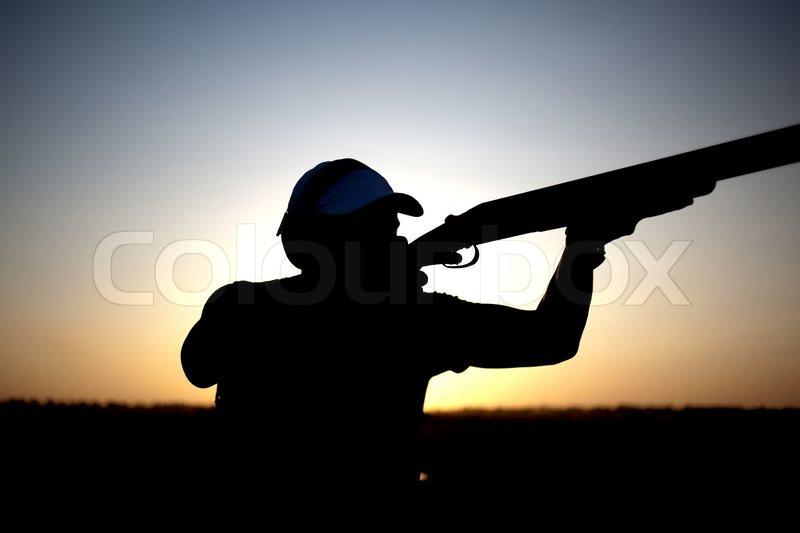 Man shoots with his gun silhouette | Stock Photo | Colourbox