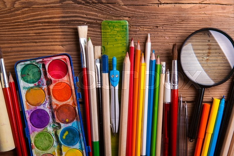 Various school and art supplies laid on table, flat lay. Studio shot on wooden background, stock photo