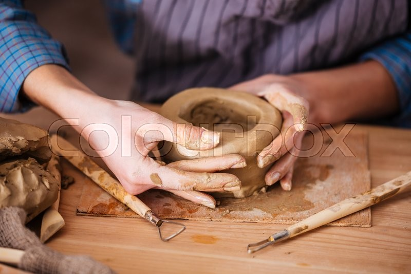 Closeup of clay pot making by hands of young woman in pottery workshop, stock photo