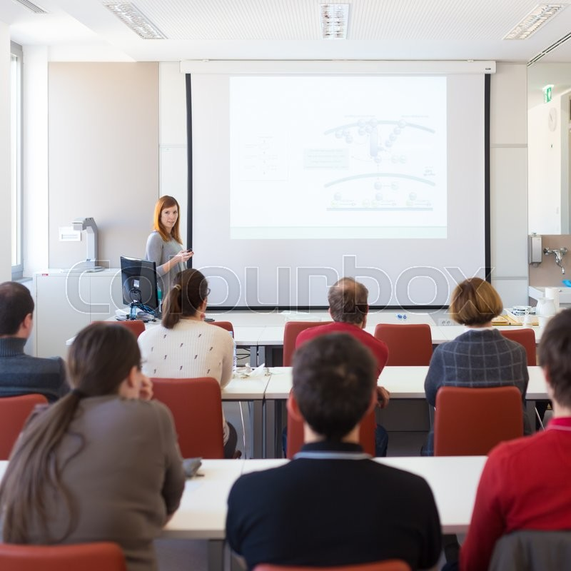 Speaker giving presentation in lecture hall at university. Participants listening to lecture and making notes, stock photo