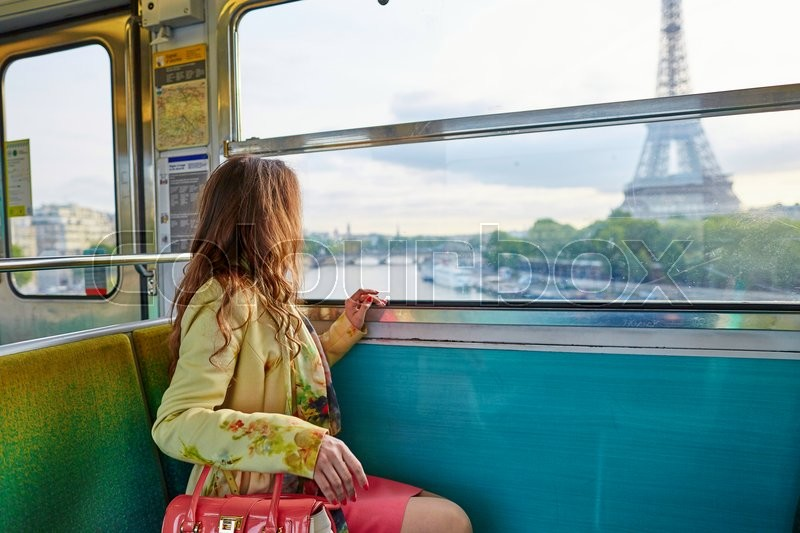 Beautiful young woman travelling in a train of Parisian underground and looking through the window at the Eiffel tower, stock photo