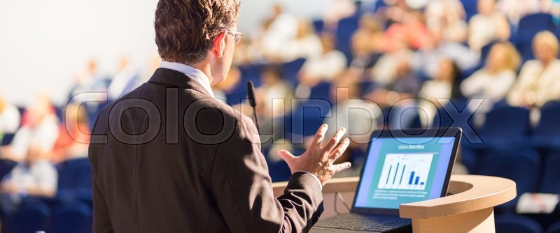 Speaker at Business Conference with Public Presentations. Audience at the conference hall. Entrepreneurship club. Rear view. Horisontal composition. Background blur, stock photo