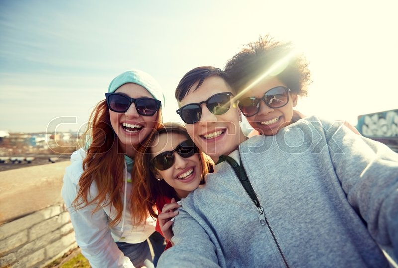 Tourism, travel, people, leisure and technology concept - group of smiling teenage friends taking selfie on city street, stock photo