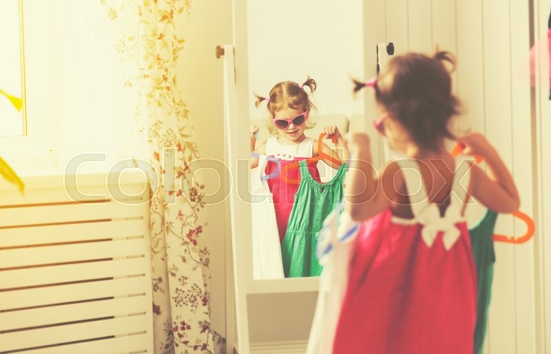 Little girl child looks into the mirror and choose dresses, stock photo
