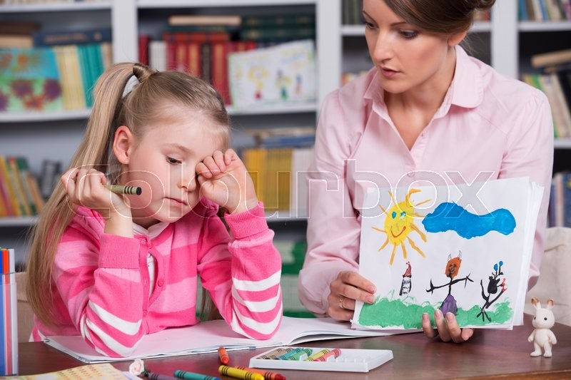 Child psychologist with a sad little girl, the doctor looks at the ...