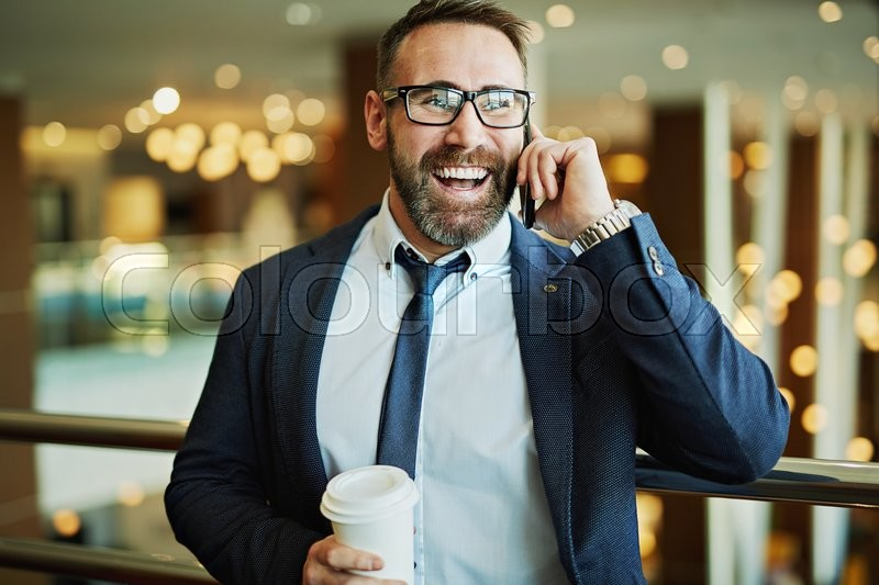 Happy businessman with plastic glass speaking on the phone, stock photo