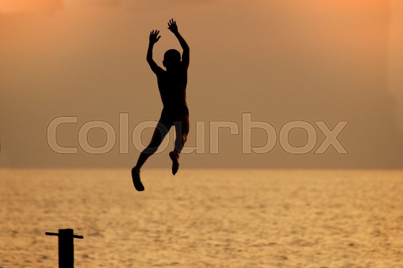 Silouette of a boy jumping from pierce in front of brightly lighted sea, stock photo