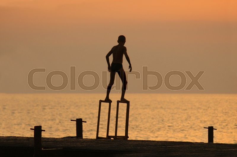 Silouette of a boy ready to dive from pierce in front of brightly lighted sea, stock photo