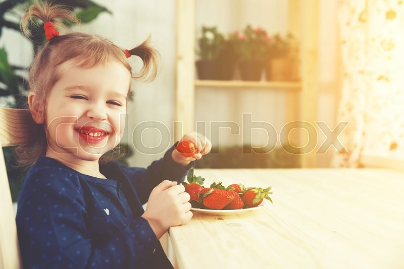 Happy child girl eats strawberries in the summer home kitchen, stock photo