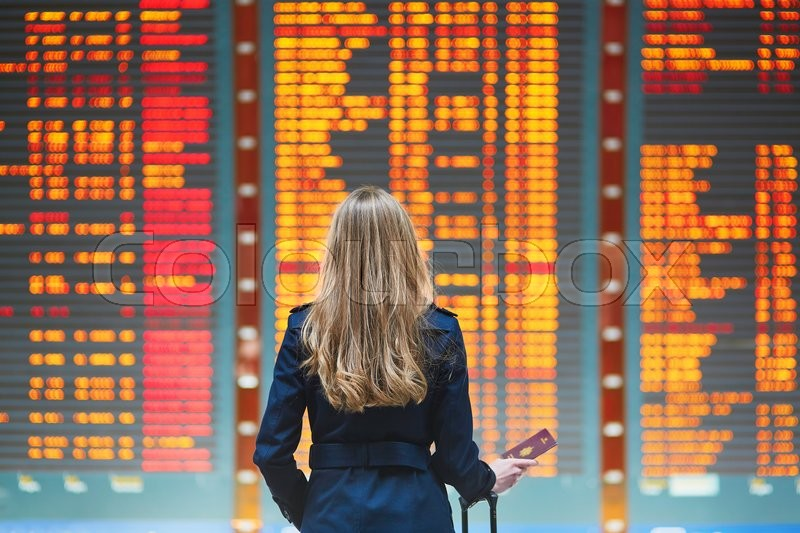 Young woman in international airport looking at the flight information board, checking her flight, stock photo