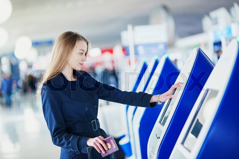 Young woman in international airport doing self check-in, stock photo
