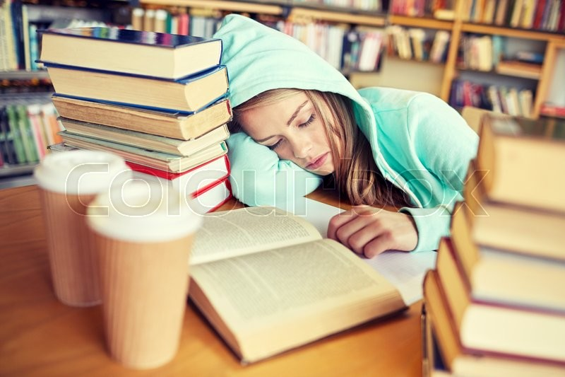 People, education, session, exams and school concept - tired student girl or young woman with books and coffee sleeping in library, stock photo
