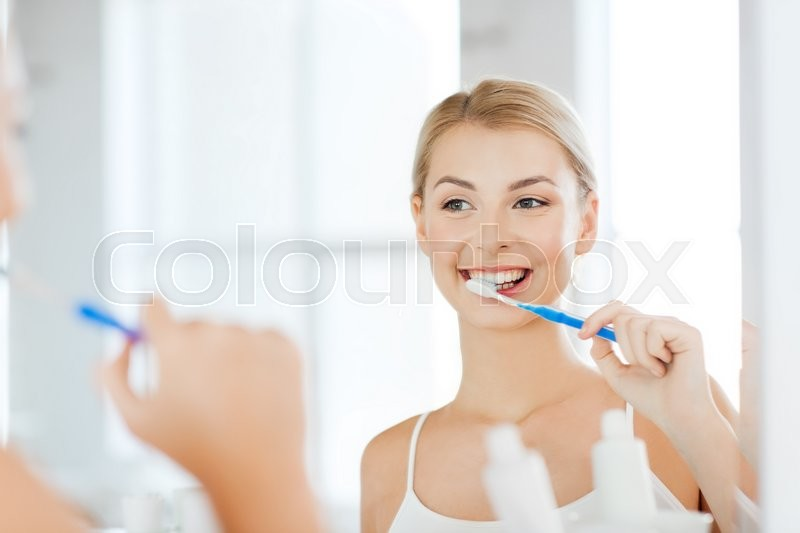 Health care, dental hygiene, people and beauty concept - smiling young woman with toothbrush cleaning teeth and looking to mirror at home bathroom, stock photo