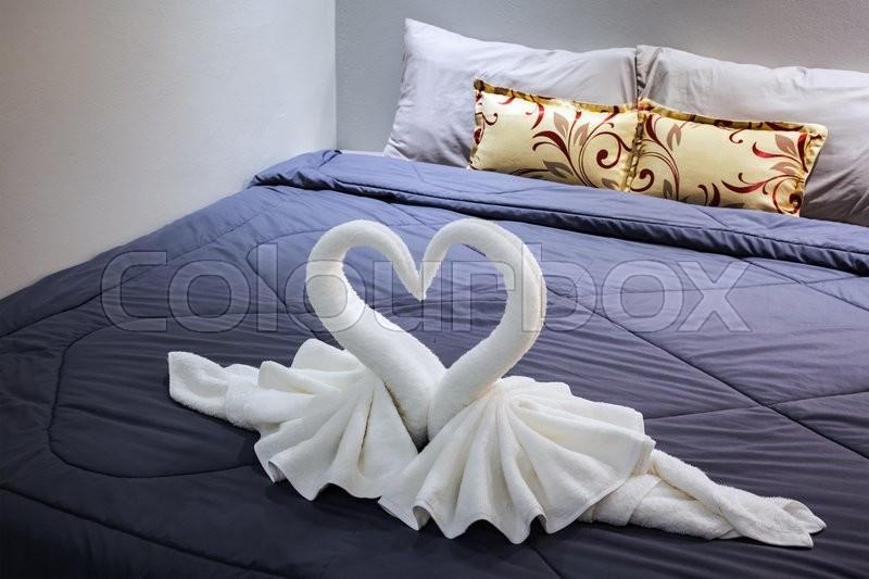 Towel folded in swan shape on bed sheet, stock photo