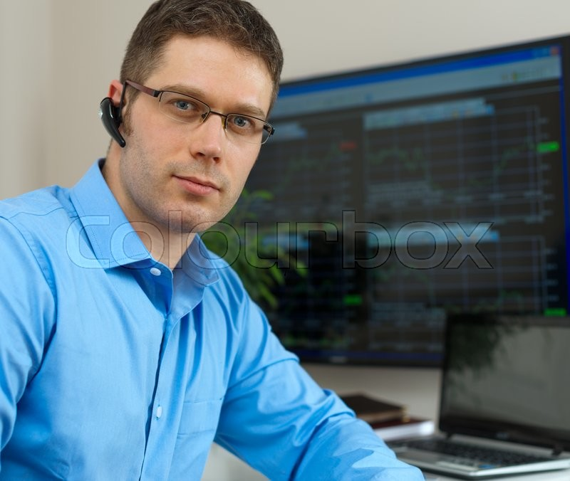 Handsome stock trader in front of computer, stock photo