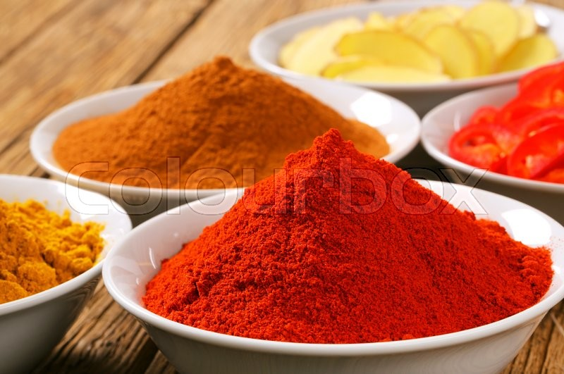 Bowls of curry powder, paprika, ground cinnamon, sliced ginger root and red pepper, stock photo