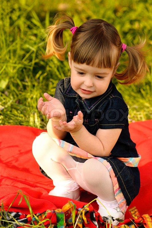 von Kleines Mädchen im Garten, sitzen auf den Teppich auf dem Rasen