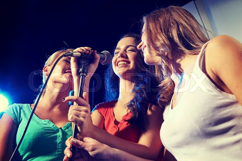 Party, holidays, celebration, nightlife and people concept - happy young women singing karaoke in night club, stock photo