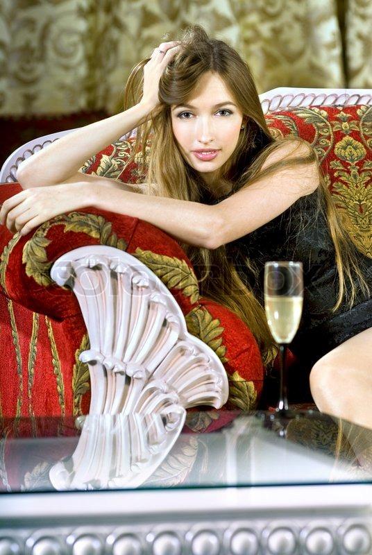 Schöne junge reiche Frau in der Nähe eines Couchtisch