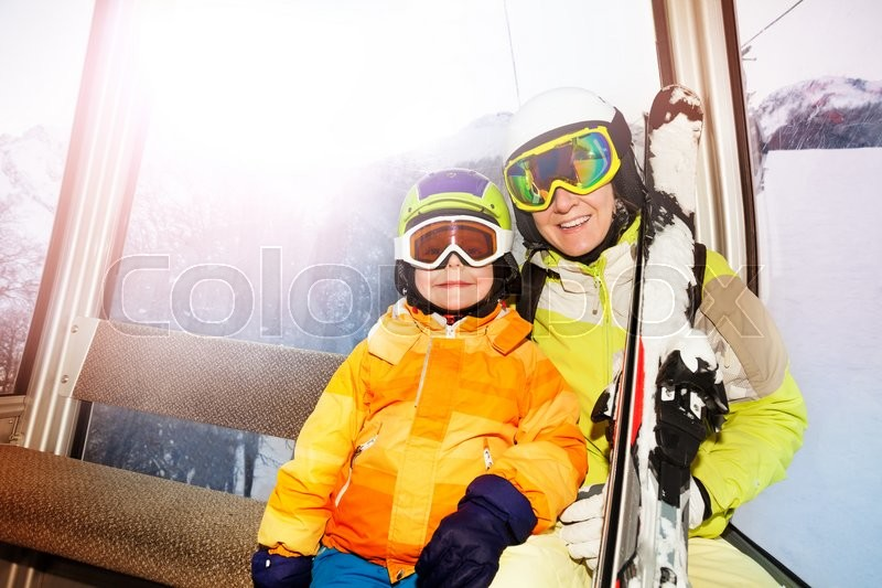 Child and mother sit in cablecar lifting on top of the mountain with ski and smiling , stock photo