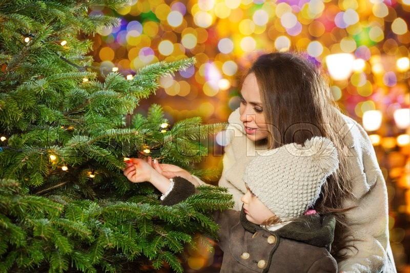 Little girl and her mother have a good time in the city park looking at new year tree in illuminated city, stock photo