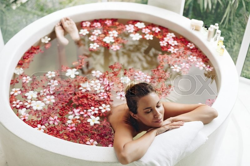 Woman relaxing in round outdoor bath with tropical flowers, organic skin care, luxury spa hotel, lifestyle photo, top view, stock photo