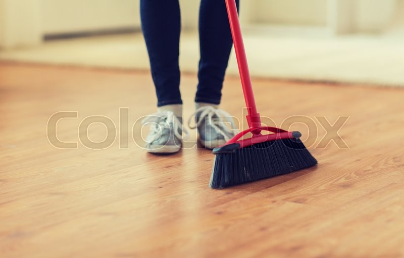 People, housework, cleaning and housekeeping concept - close up of woman legs with broom sweeping floor at home, stock photo