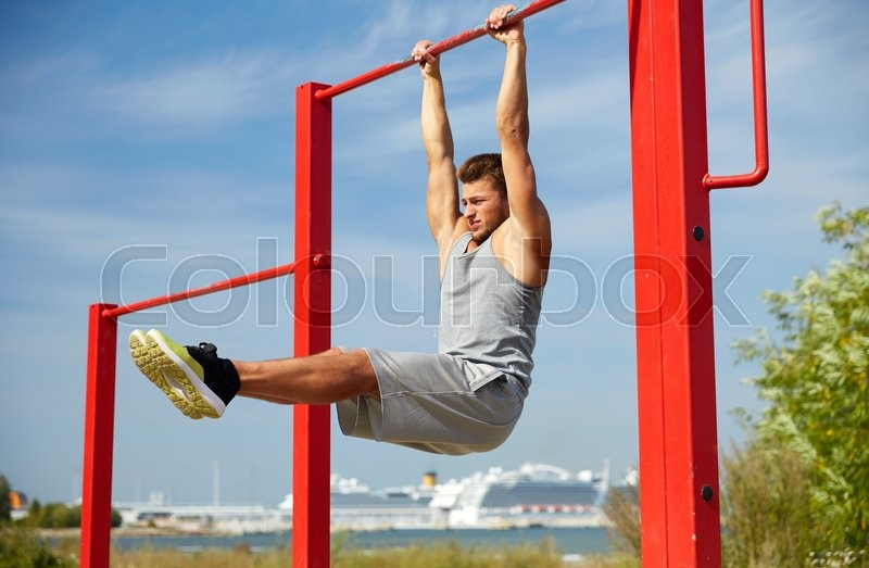 Fitness, sport, exercising, training and lifestyle concept - young man doing abdominal exercise on horizontal bar in summer park, stock photo
