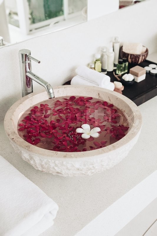 Luxury hotel bathroom details: sink with flowers, spa decoration ...