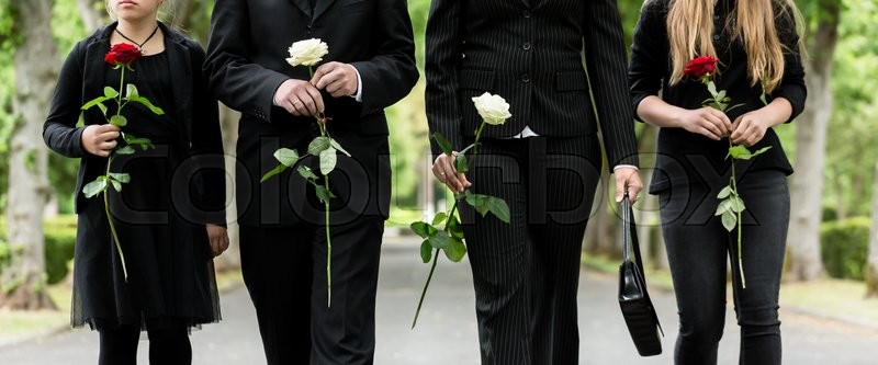 Torso of family on cemetery mourning holding red and white roses in hands, stock photo