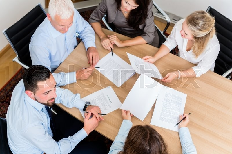 Lawyers having team meeting in law firm reading documents and negotiating agreements, stock photo