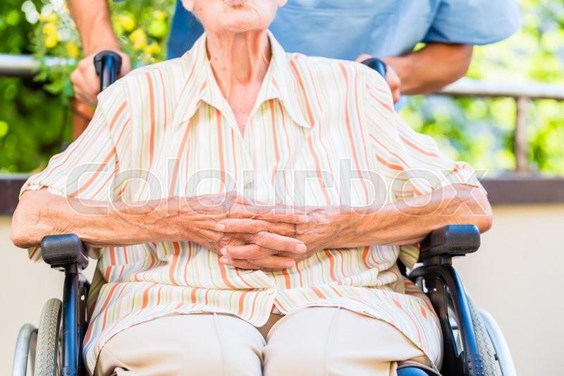 Geriatric nurse pushing senior lady in wheel chair thru home, stock photo