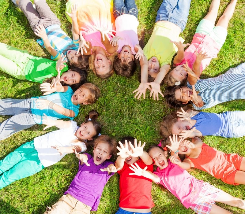 14 kids laying in a circle in the grass with happy faces for Immagini di api per bambini