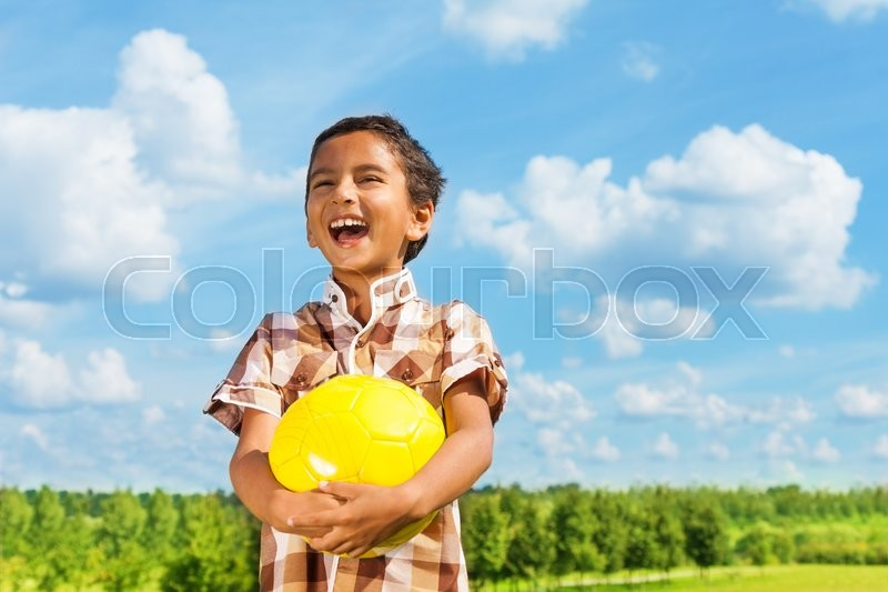 Laughing dark boy holding yellow volley ball standing in the park on sunny day with blue clouds on background, stock photo