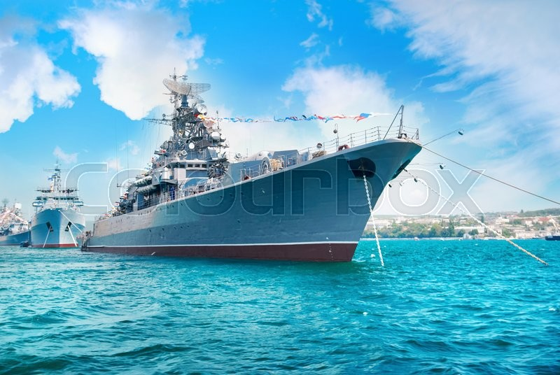 Military navy ship in the bay. Military sea landscape with blue sky and clouds, stock photo