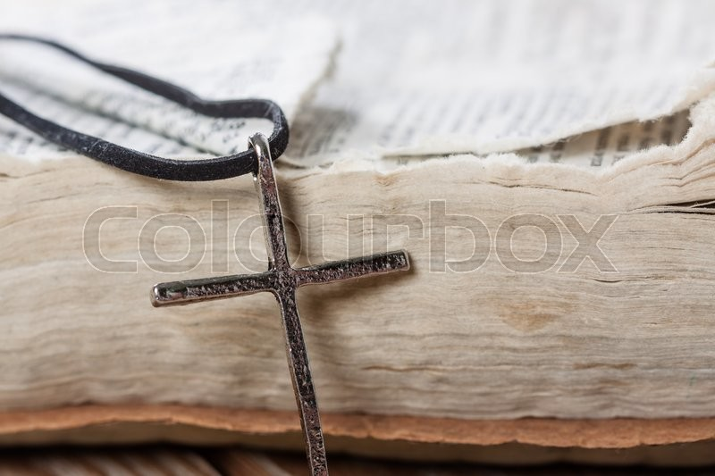 Silver christian cross on bible. Religious concept, stock photo