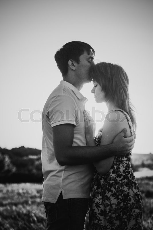 Black white photography romantic couple standing and kissing on background summer meadow sunset stock photo colourbox