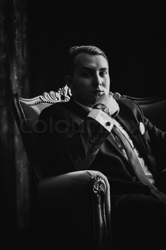 Black white photography portrait of man in black classic suit on a dark background, stock photo