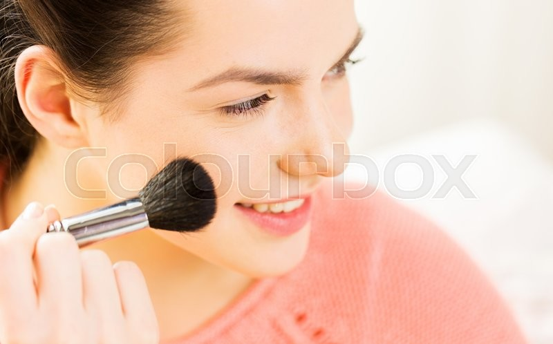 Beauty, make up, cosmetics and people concept - close up of smiling young woman face applying blush with makeup brush, stock photo