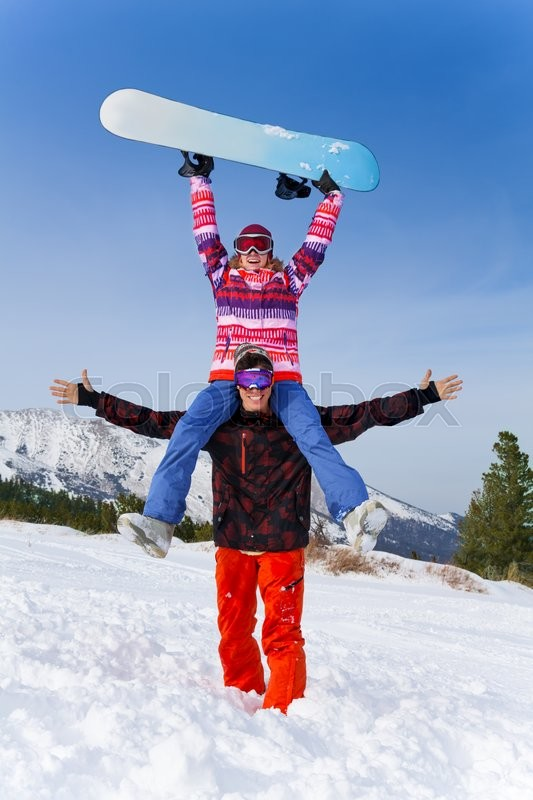 Excited snowboarder embracing arms in emotions with girl sitting on his shoulders who holds snowboard in her arms high, stock photo