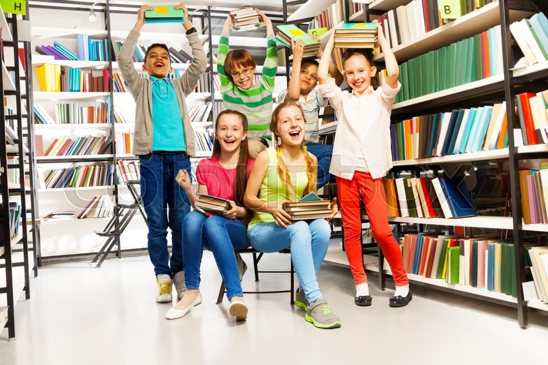 Excited happy laughing children in library with positive emotions and holding arms with books up, stock photo