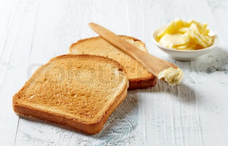 Slices of toast bread and butter on wooden table, stock photo