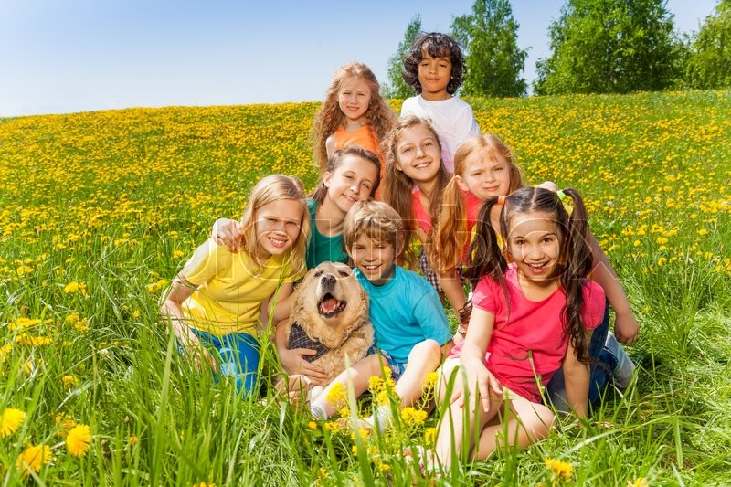 Cheerful kids with dog sitting on the green grass in summer, stock photo