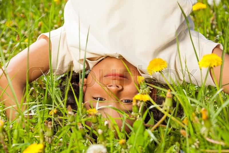 Cute curly boy standing upside down on head in dandelions field in summer, stock photo