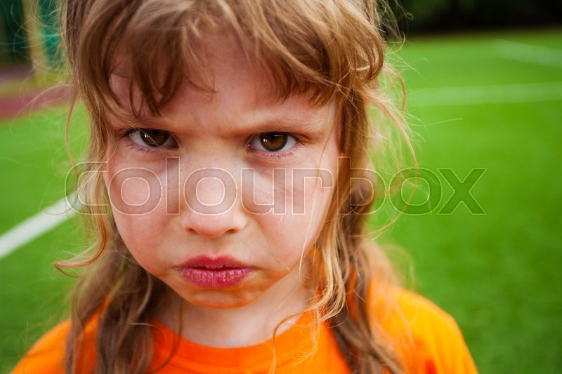 Sad angry girl portrait looking straight on the background of green field, stock photo