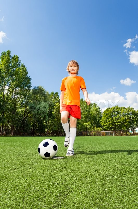 happy boy kicking football with one leg on green grass of field in