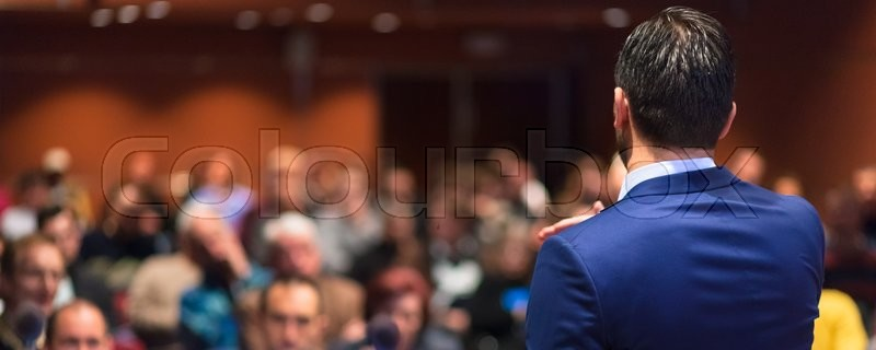 Rear view of speaker giving a talk on corporate Business Conference. Audience at the conference hall. Business and Entrepreneurship event. Panoramic composition, stock photo