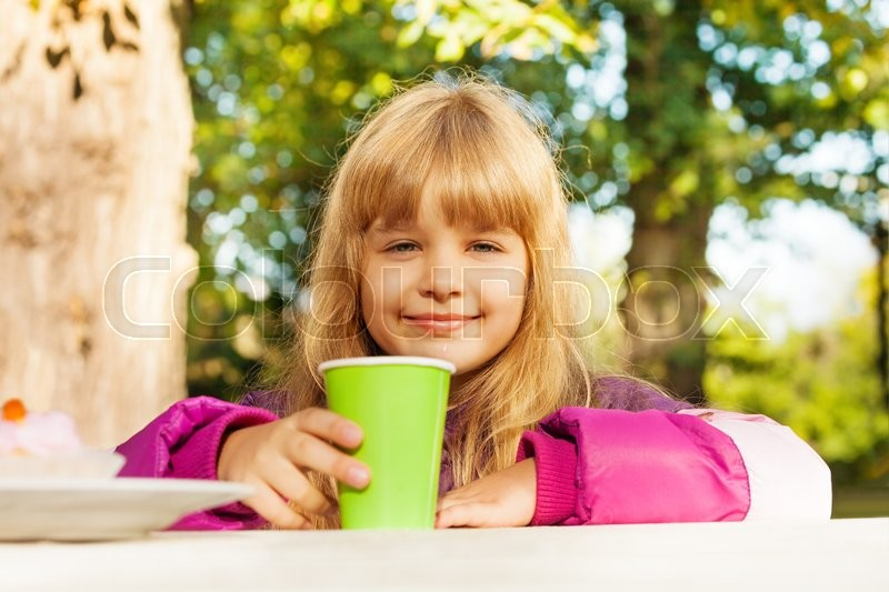 Cute small blond girl with green cup sitting at the table and drinking tea in park, stock photo