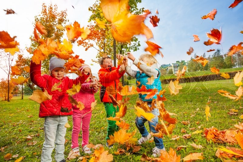 Active group of children playing with flying maple leaves and enjoying wonderful autumn day, stock photo